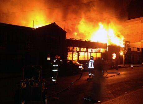 Hasiči se snaží uhasit požár restaurace, který vzplál po zemětřesení o síle 8,2 Richterovy stupnice