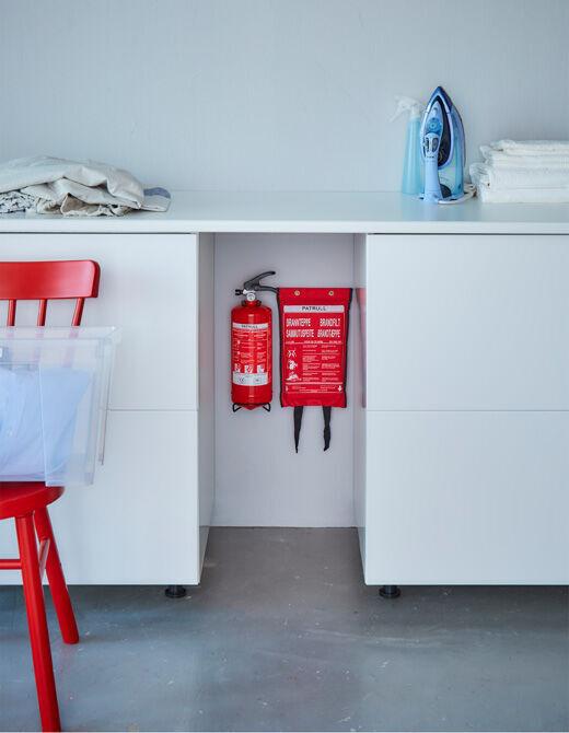 Na stěně mezi dvěma skříňkami je zavěšený hasicí přístroj a hasicí deka.