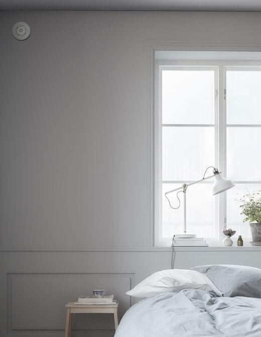 Vysoko na stěně blízko postele a schůdků je detektor kouře.