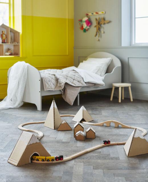 V dětském pokoji projíždí dětský vláček kartonovými horami