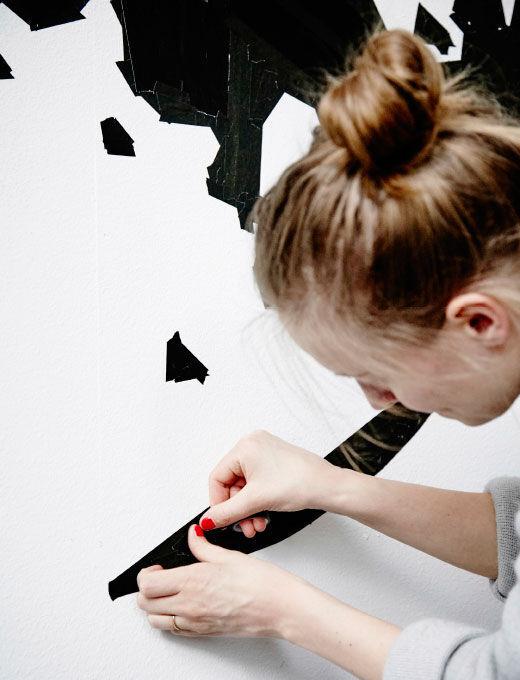 Agnes aplikuje lepicí pásku na zeď