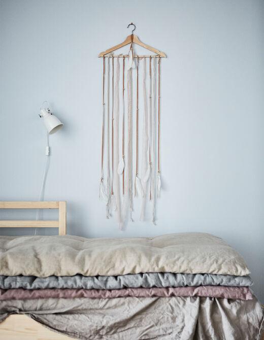 Hledáte nové nápady na dekoraci? Vytvořte si ozdobný věšák na předměty! IKEA má spoustu ramínek, např. dřevěné ramínko BUMERANG. Pro ozvláštnění doplňte provázky.